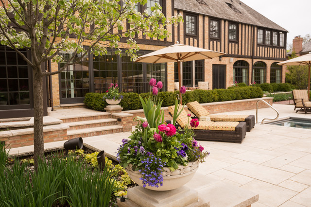 This is an example of a large traditional full sun backyard stone retaining wall landscape in Chicago for spring.