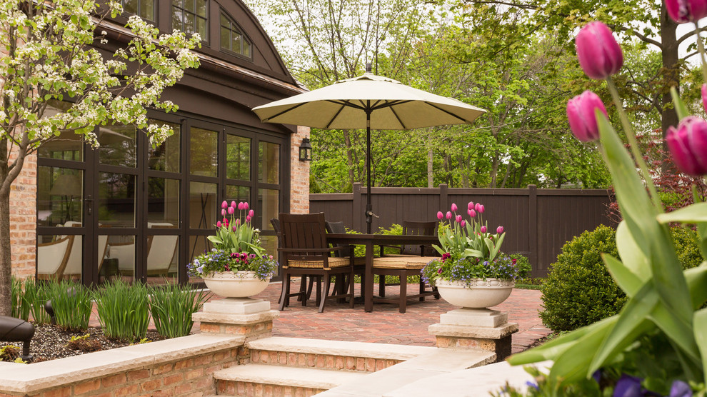 Design ideas for a large traditional full sun backyard brick retaining wall landscape in Chicago for spring.