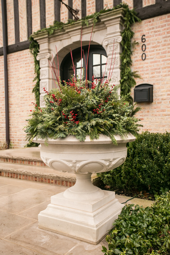 This is an example of a large traditional full sun front yard stone landscaping in Chicago for winter.