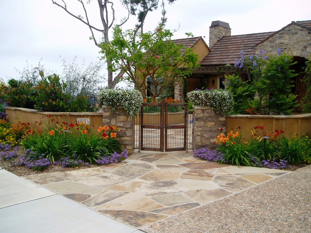 Photo of a mediterranean full sun front yard stone landscaping in San Diego.