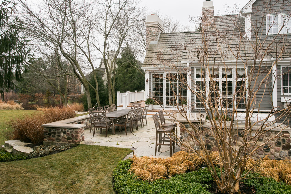 Design ideas for a mid-sized transitional full sun backyard stone landscaping in Chicago for winter.