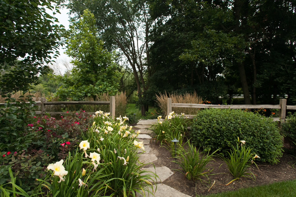 Inspiration for a mid-sized farmhouse full sun side yard stone landscaping in Chicago for summer.