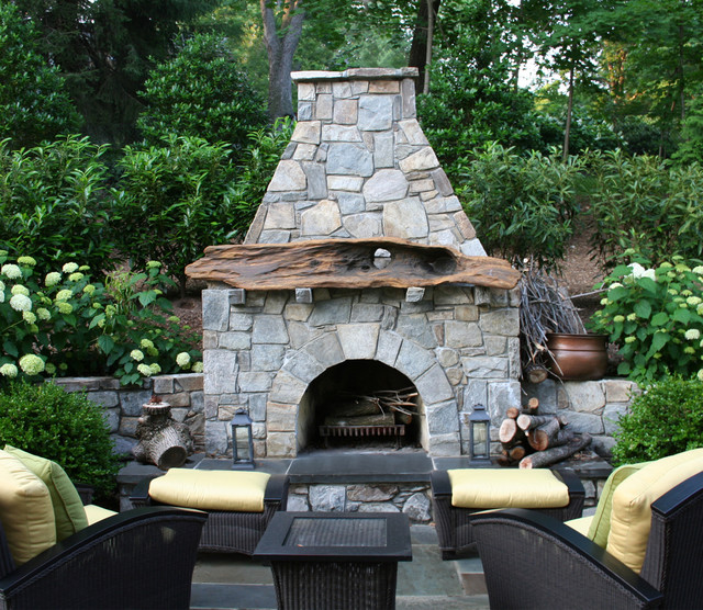 driftwood mantel on fieldstone outdoor fireplace