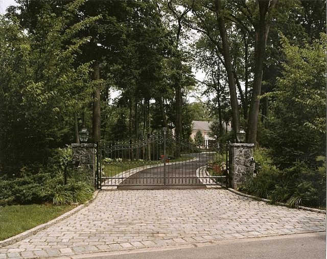 Driveway entrance with custom iron gates stone piers and cobblestone