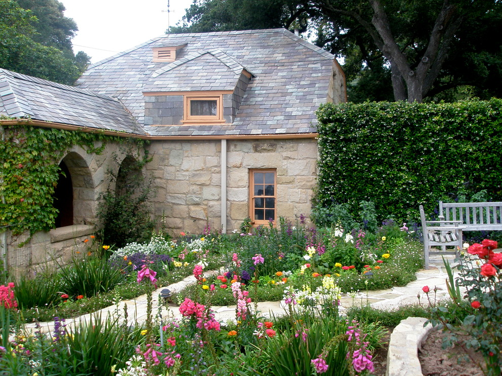 This is an example of a farmhouse backyard stone landscaping in Santa Barbara for summer.