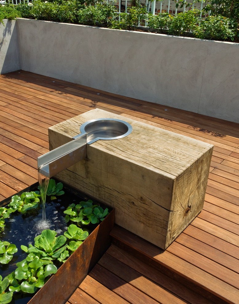 This is an example of a large modern full sun rooftop water fountain landscape in New York with decking.