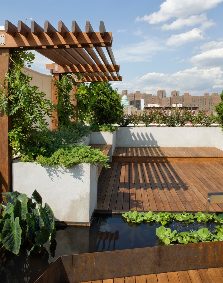 Inspiration for a large contemporary full sun rooftop water fountain landscape in New York with decking.