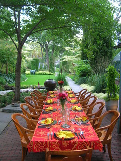Outdoor dining room with festive table settings for 12.