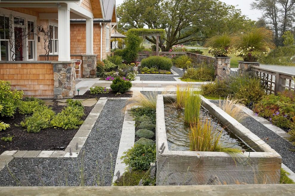 Inspiration for a large traditional full sun front yard concrete paver water fountain landscape in Seattle for summer.