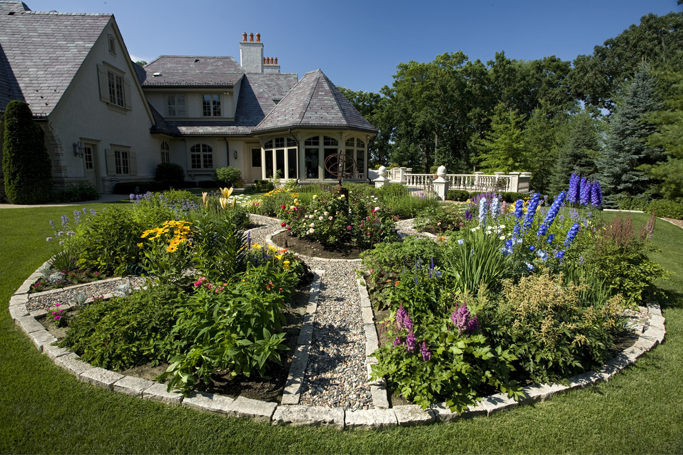 Inspiration for a huge traditional backyard flower bed in Minneapolis.