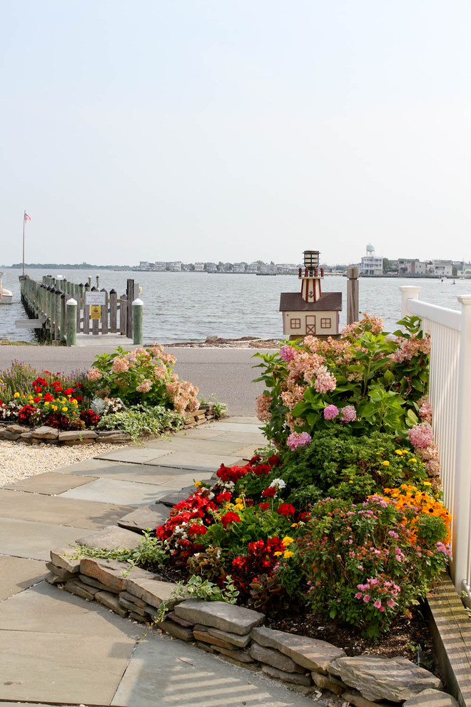 This is an example of a coastal full sun front yard stone flower bed in Philadelphia for summer.