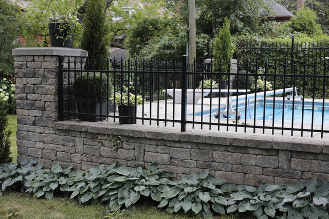 Field stone wall with ornamental iron fence modern