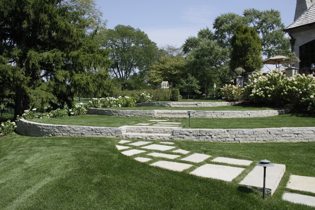 Inspiration for a huge traditional partial sun hillside stone retaining wall landscape in Chicago.