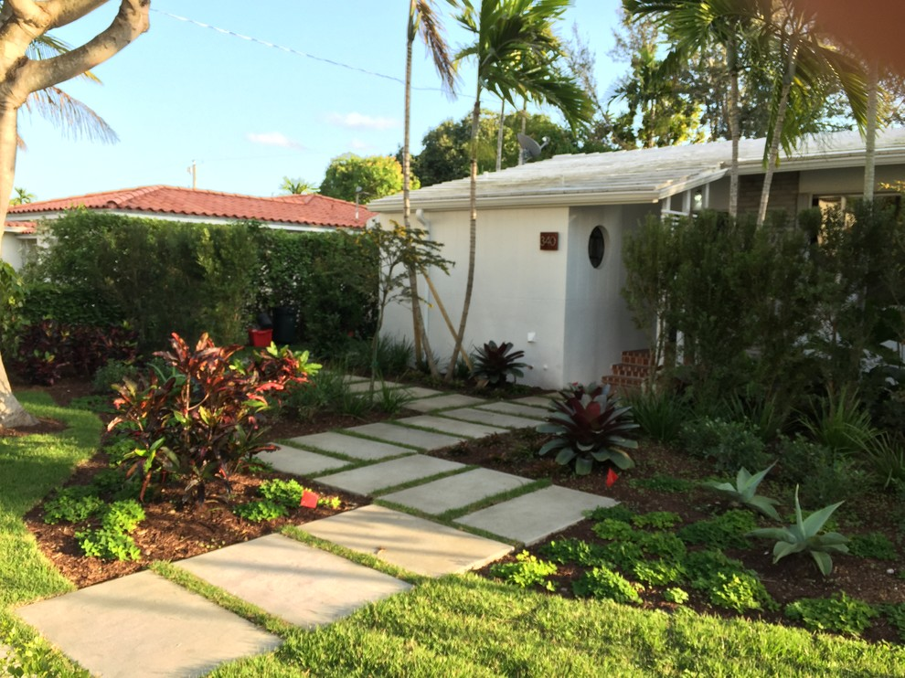 This is an example of a mid-sized modern partial sun front yard concrete paver landscaping in Miami.