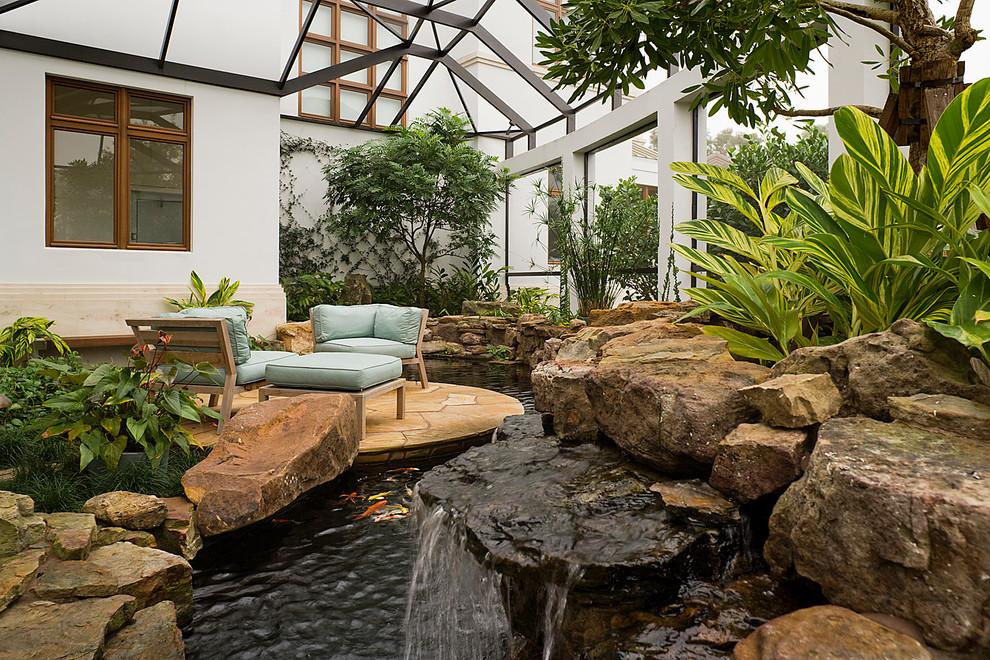 Design ideas for a large mediterranean partial sun backyard water fountain landscape in Miami.