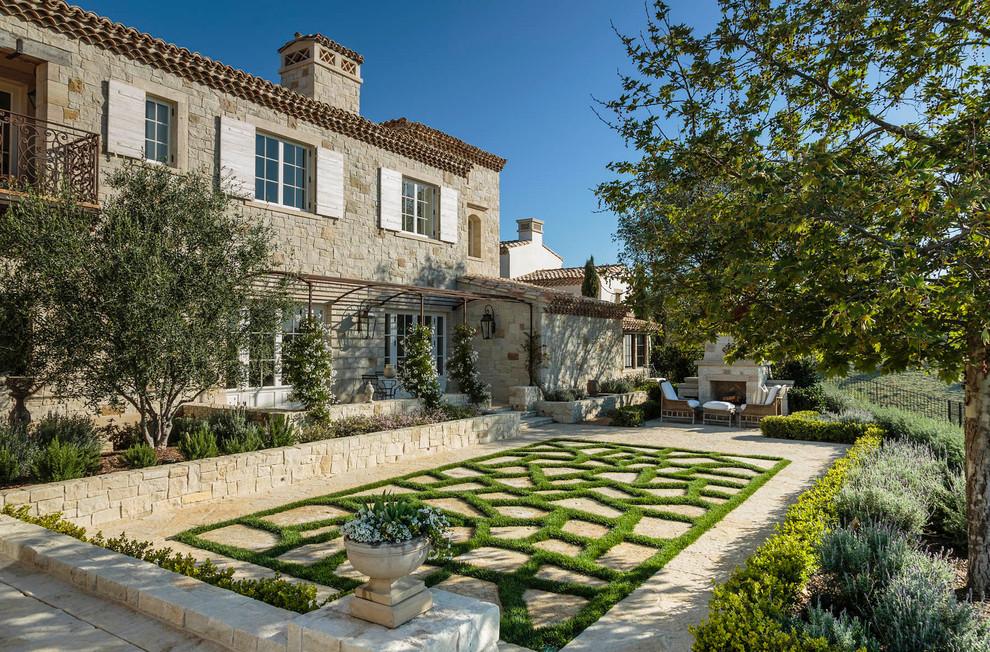 Mediterraner Garten mit Natursteinplatten und Kamin in Orange County