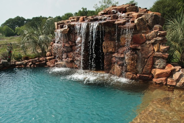 Lagoon Style Swimming Pool With Waterfall Grotto With Spa Inside.  Traditional Landscape