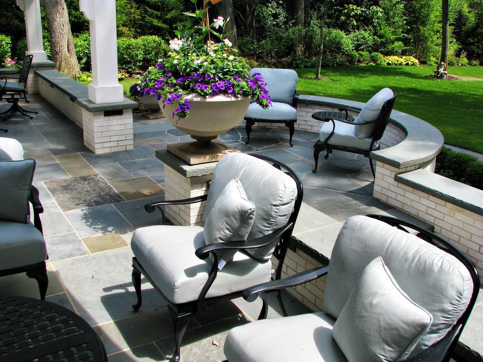 Modelo de jardín clásico, en patio trasero, con muro de contención y adoquines de piedra natural