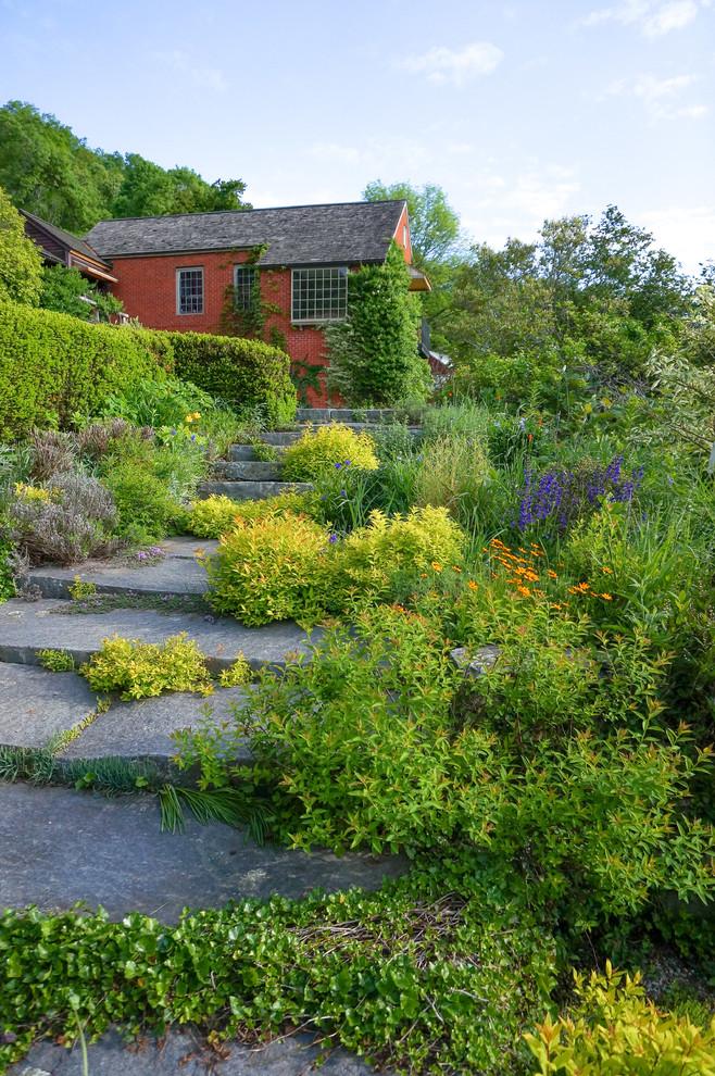 Design ideas for a farmhouse full sun backyard stone landscaping in New York.