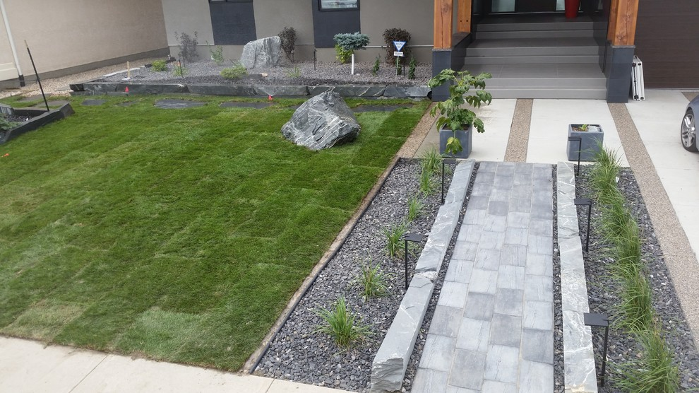 This is an example of a large traditional front yard concrete paver driveway in Other.