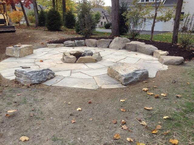 large fire pit area with boulder tables and rock wall