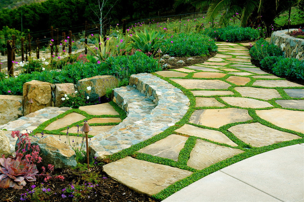 Inspiration for a mediterranean hillside stone landscaping in San Diego.