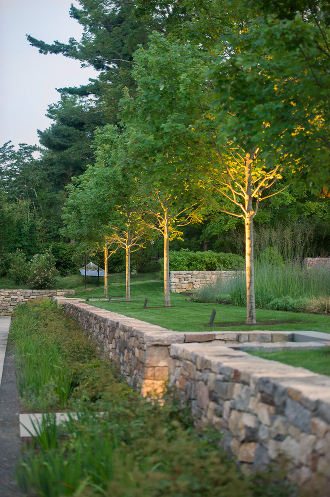 This is an example of a mid-sized contemporary partial sun backyard stone landscaping in New York.