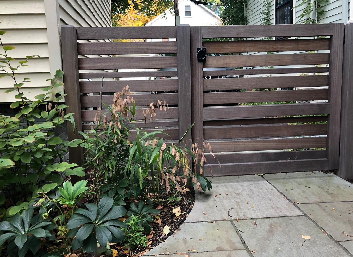 Mahogany garden gate separates driveway from garden