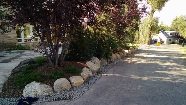 This is an example of a medium sized traditional back driveway garden in Denver with a garden path and natural stone paving.