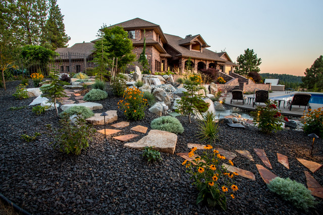 This is an example of a large traditional backyard gravel landscaping in Seattle.