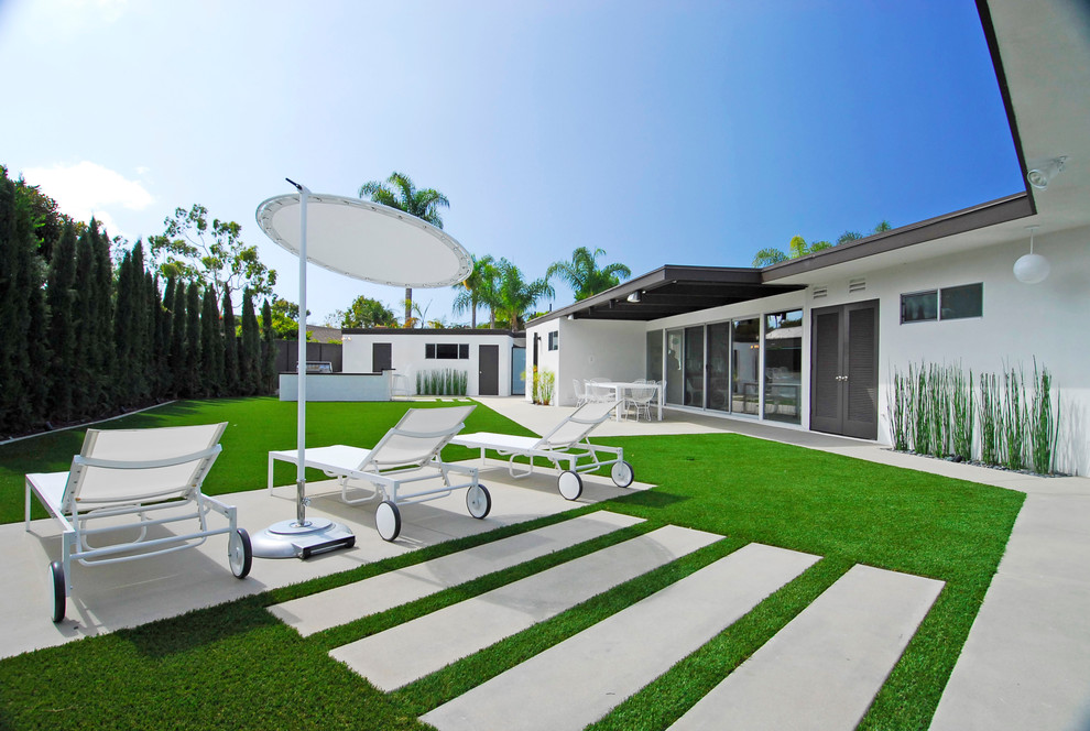 Photo of a large contemporary full sun backyard concrete paver landscaping in Orange County.