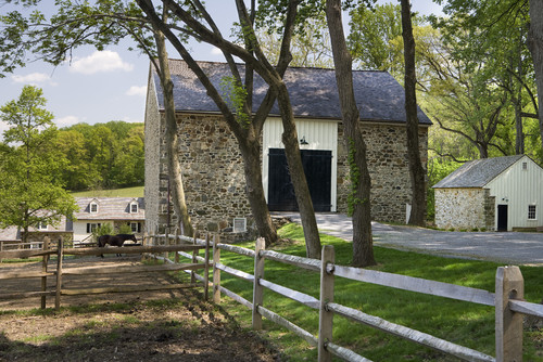 A beautiful stone building with tall trees and a horse pasture enclosed by a series of sturdy split rail mortised fences.