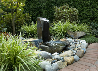 Small natural looking water fountain with lots of rocks.