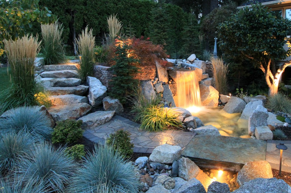 This is an example of a contemporary backyard river rock waterfall in Seattle.