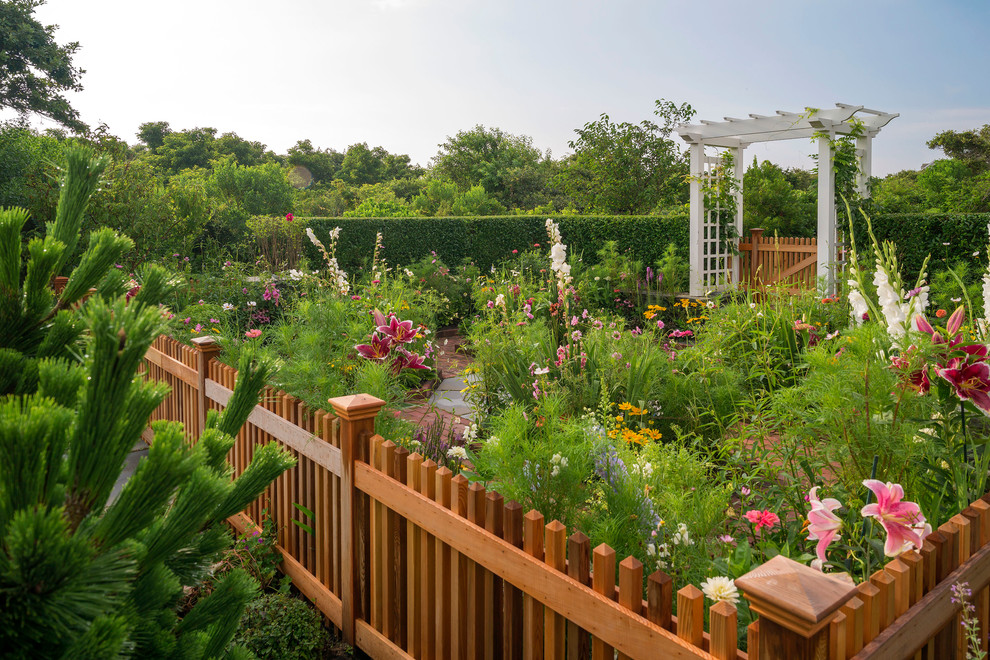 Photo of a mid-sized coastal full sun backyard brick and wood fence formal garden in Boston for spring.