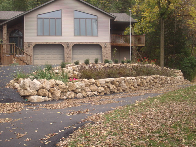 Natural Limestone boulder retaining wall with built in stairway traditional-landscape