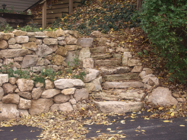 Natural limestone boulder retaining wall with built in for Limestone landscape rock