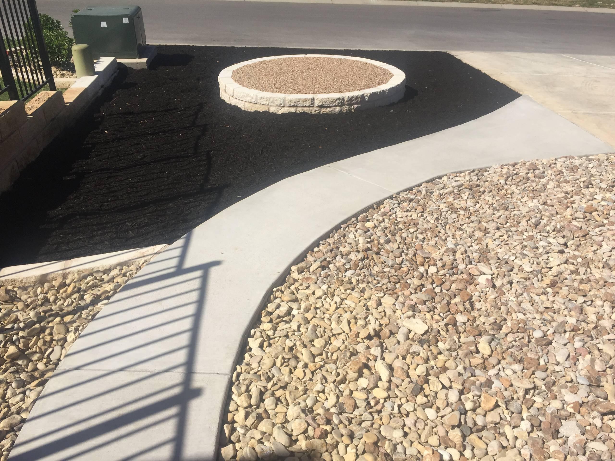 New concrete sidewalk & limestone raised bed w/ different gravels