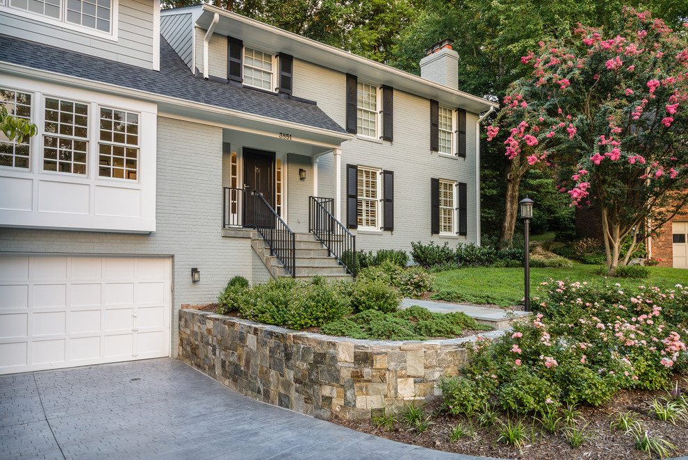 This is an example of a mid-sized contemporary full sun front yard stone landscaping in DC Metro for summer.