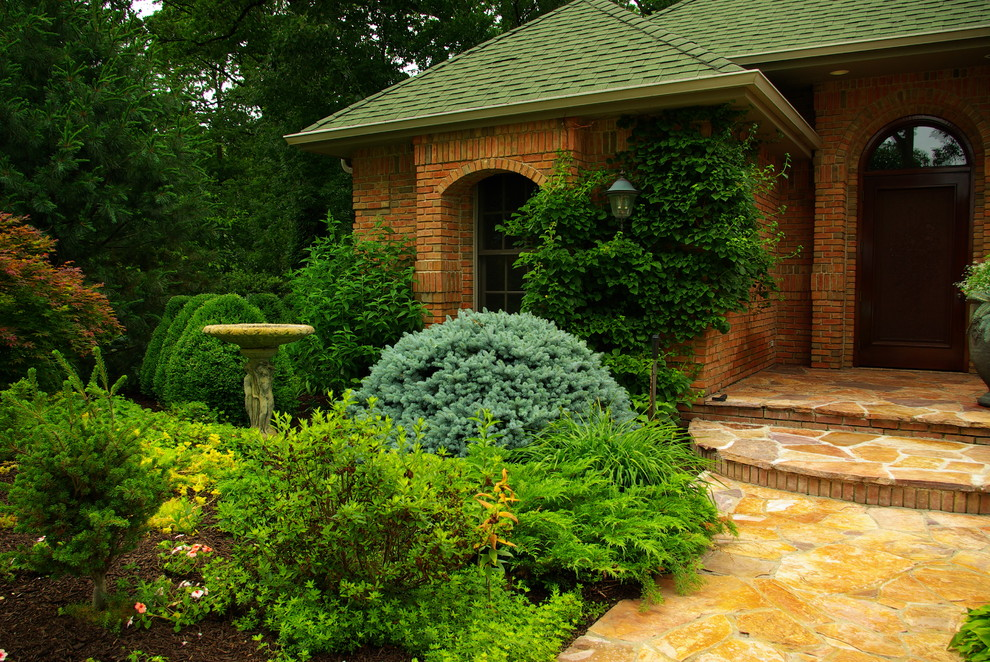 This is an example of a large traditional shade front yard stone landscaping in Chicago for summer.