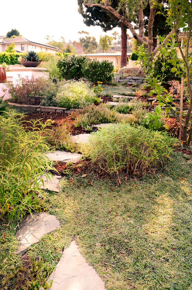 This is an example of a mid-sized mediterranean drought-tolerant and full sun front yard stone garden path in Los Angeles.