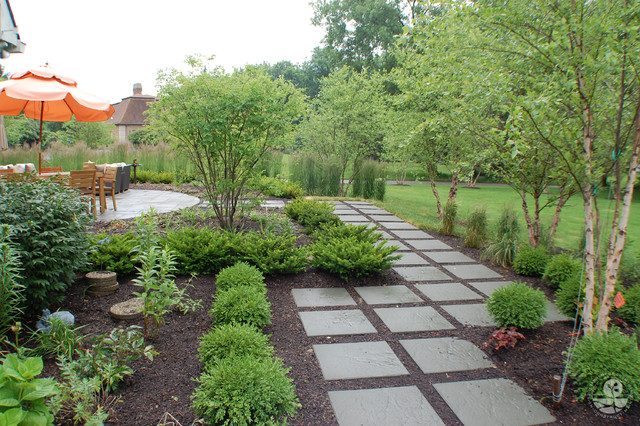 This is an example of a large contemporary full sun backyard stone landscaping in Indianapolis for spring.