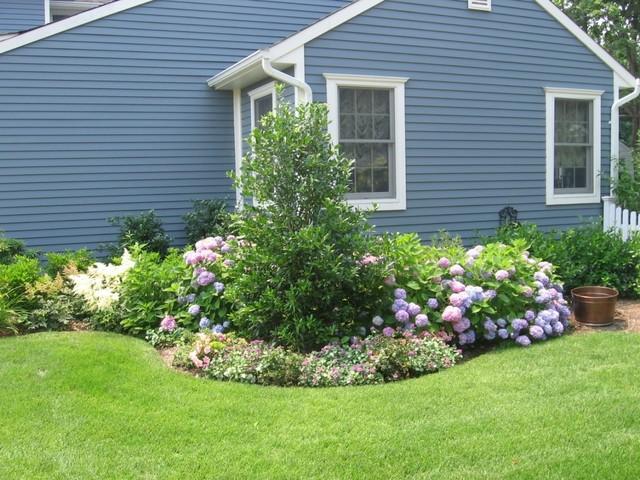 Foto på en vintage trädgård i slänt, med en trädgårdsgång och naturstensplattor