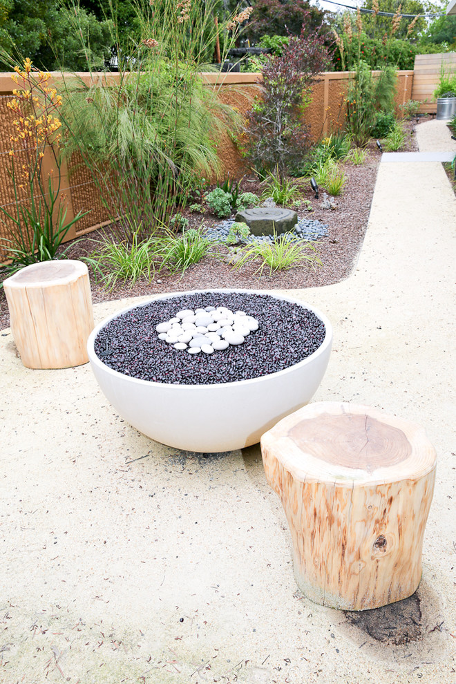 This is an example of a mid-sized mid-century modern drought-tolerant and full sun front yard concrete paver landscaping in San Francisco with a fire pit.