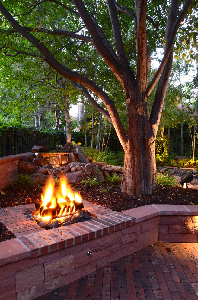 Inspiration for a traditional backyard brick landscaping in Denver with a fire pit.