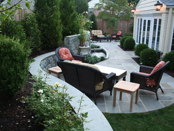 Patio with curved fieldstone retaining wall water feature for Curved garden wall ideas
