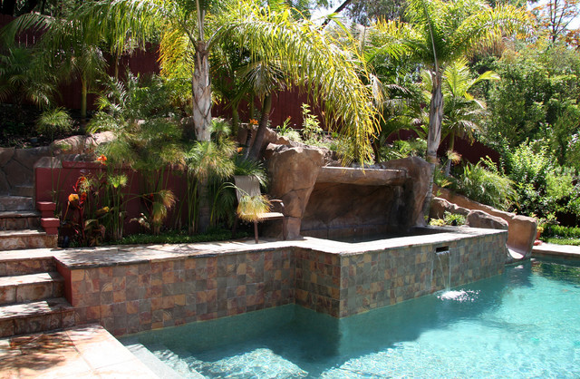 Pool with hillside slide and raised spa tropical for Landscaping rocks in los angeles