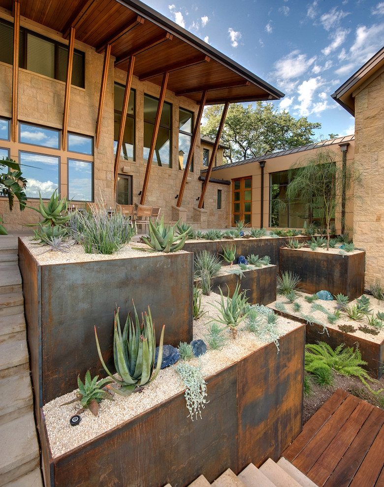 This is an example of a southwestern drought-tolerant and full sun hillside concrete paver landscaping in Austin.