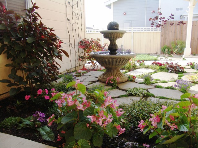 This is an example of a mid-sized transitional backyard stone water fountain landscape in San Luis Obispo.