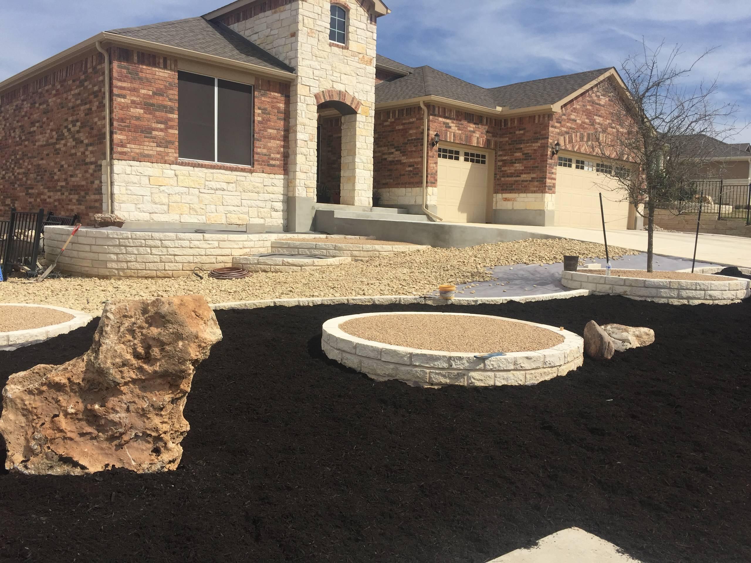 Progress pic of new concrete entryway, limestone raised beds & Xeriscape